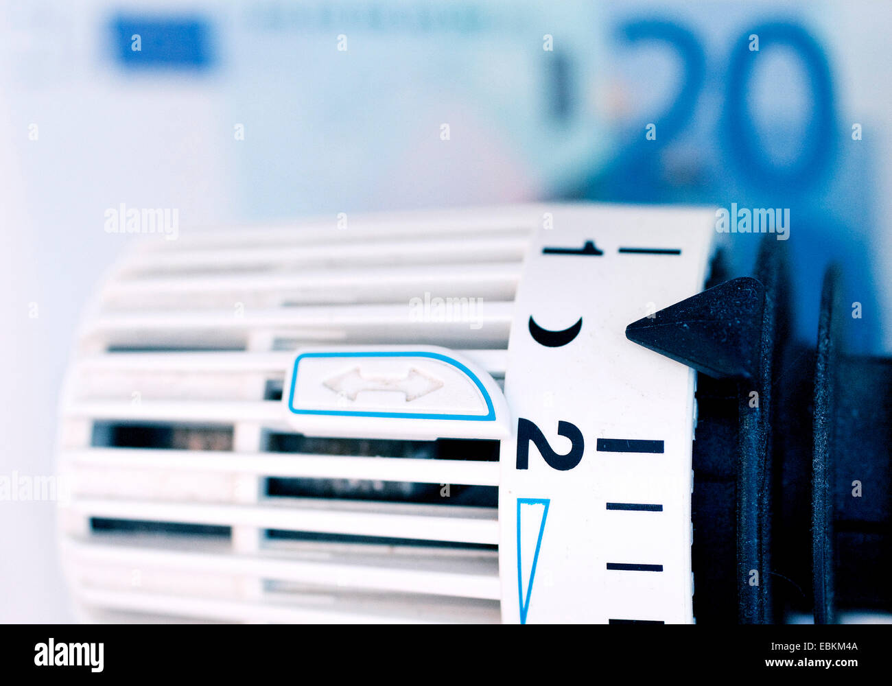 radiator thermostat and bank notes, symbol picture for heating costs, Germany - Stock Image