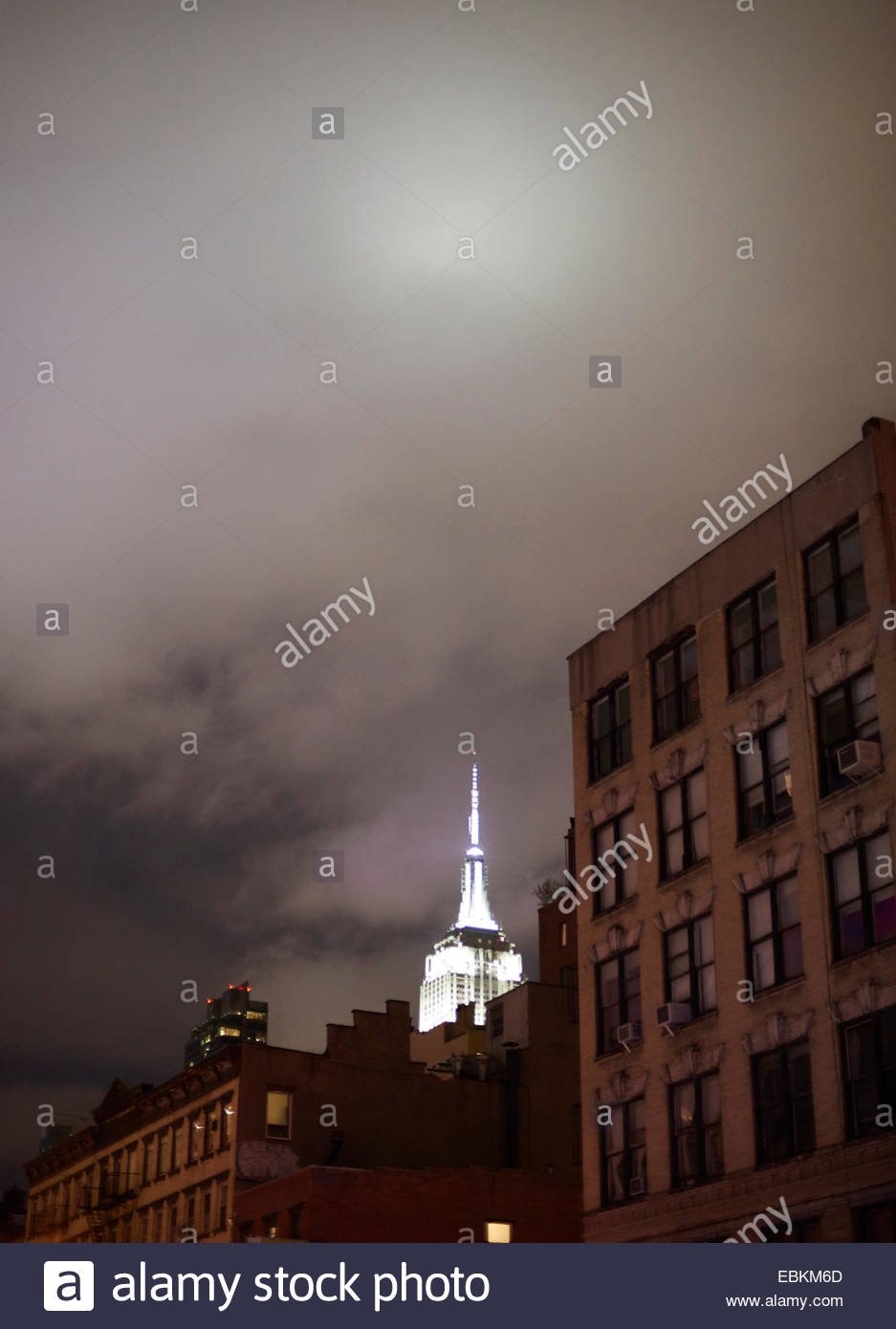 The Empire State Building illuminated at night with buildings in foreground New York USA Stock Photo