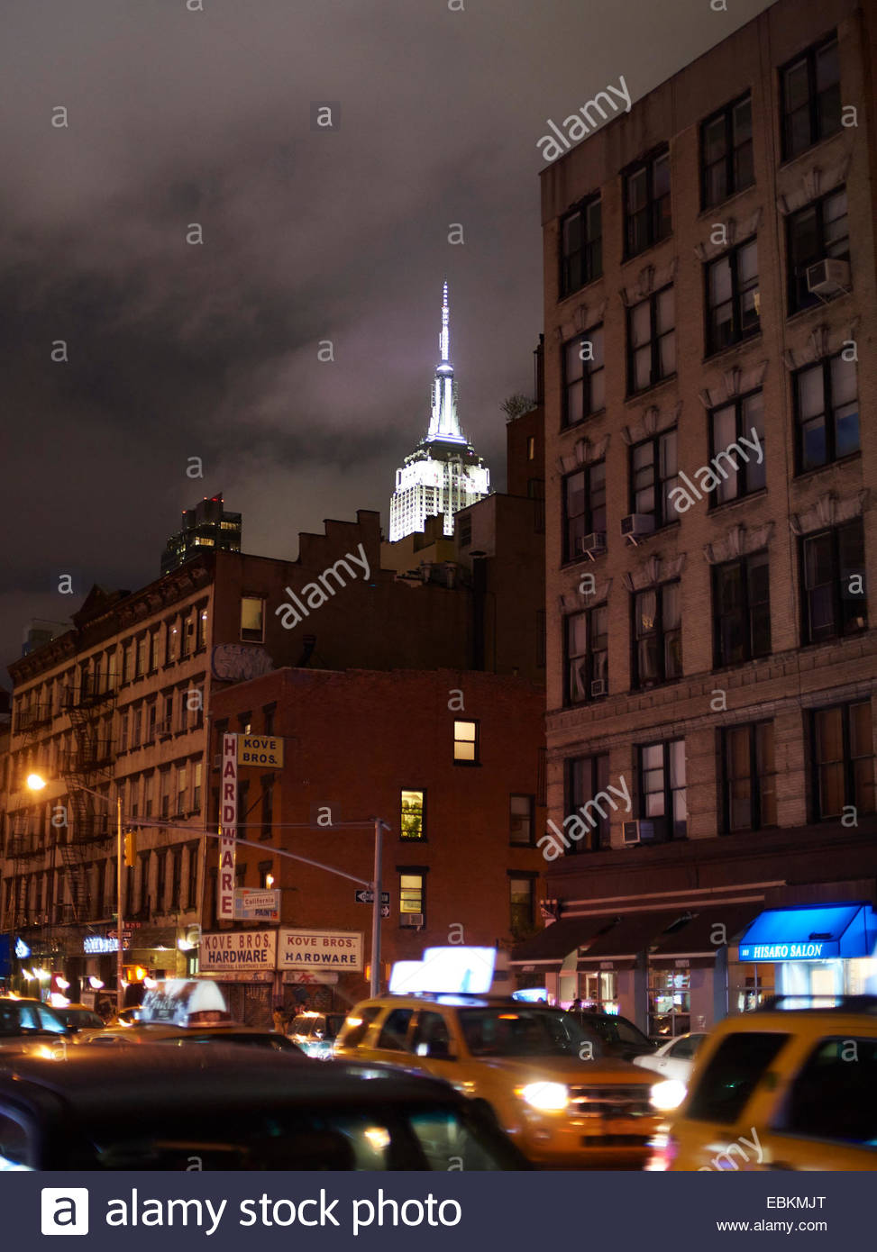 The Empire State Building illuminated at night with buildings in foreground New York USAStock Photo