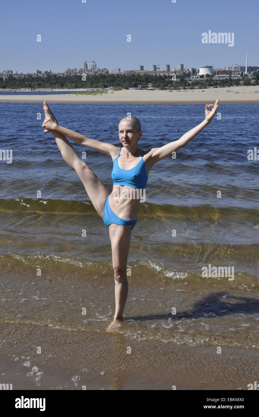 Bald woman standing in yoga position called Extended Hand-To-Big-Toe Pose, or utthita hasta padangusthasana on a - Stock Image