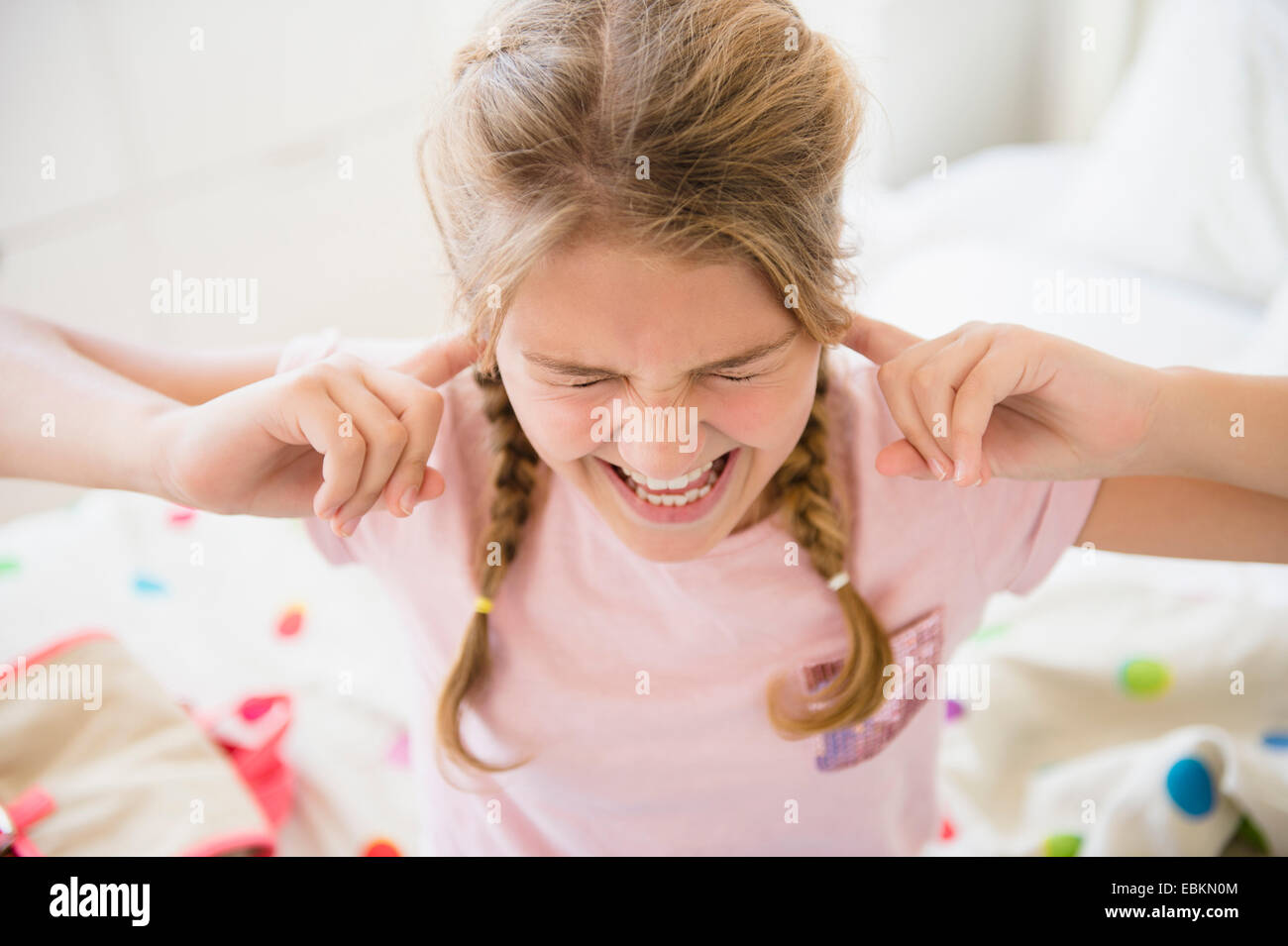 Angry girl (12-13) in bedroom - Stock Image