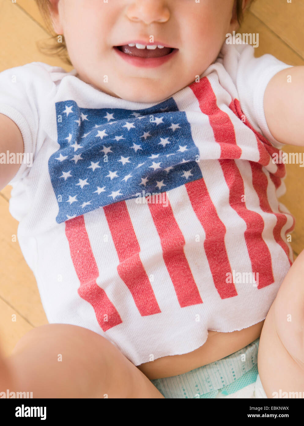 Studio shot of little girl (18-23 months) in t-shirt with American flag - Stock Image