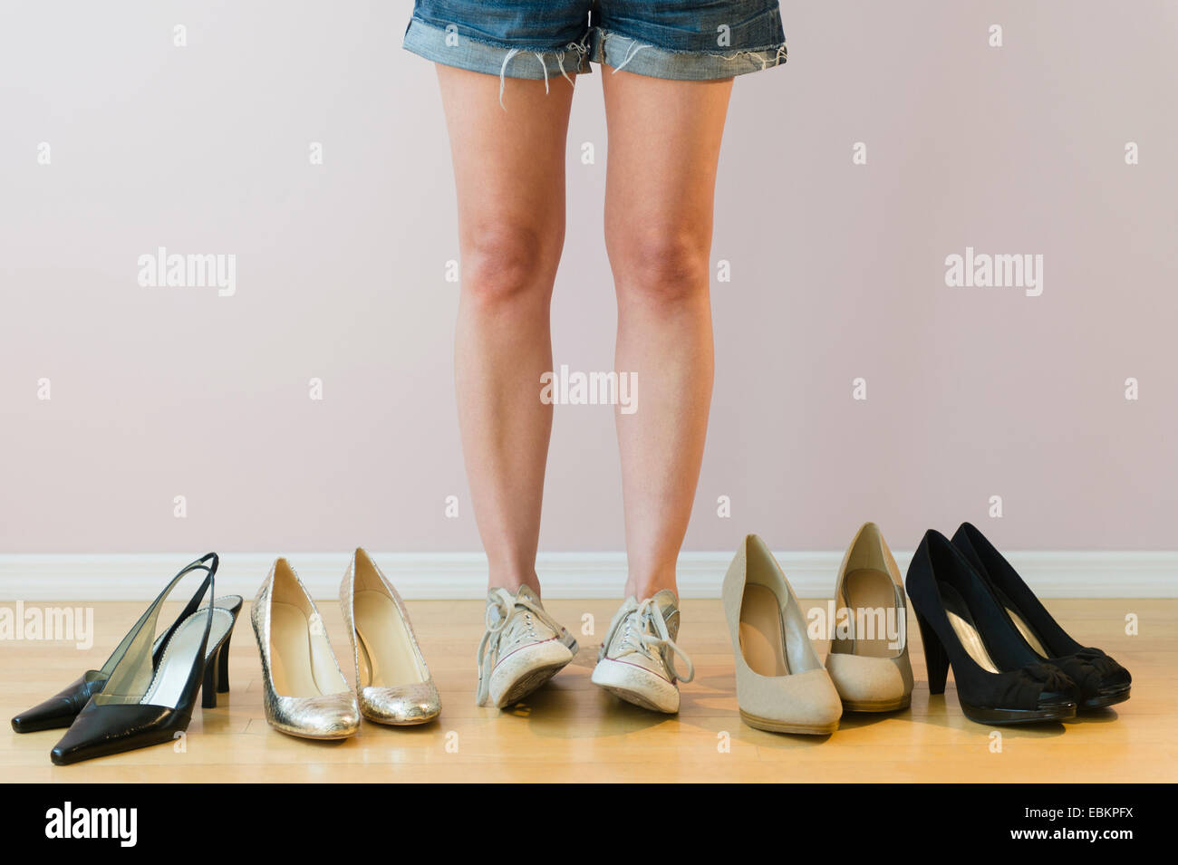 Studio shot of woman with pairs of shoes - Stock Image