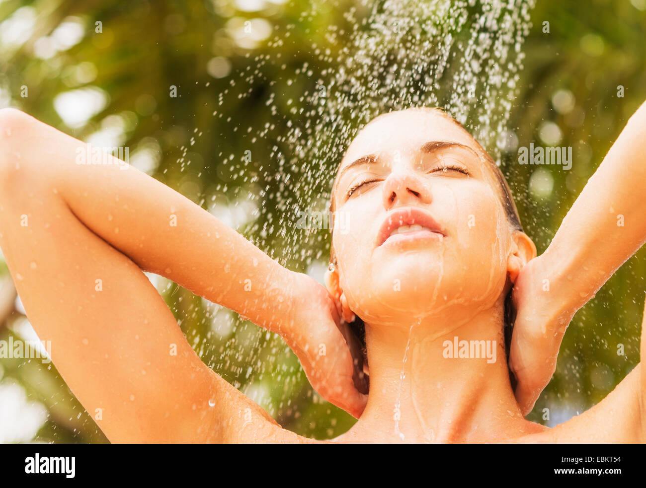 Woman taking shower outdoors - Stock Image