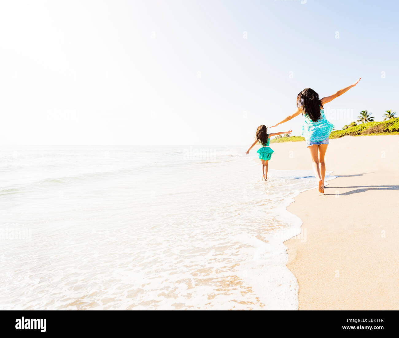 USA, Florida, Jupiter, Rear view of girl (6-7) and her mom running on beach - Stock Image