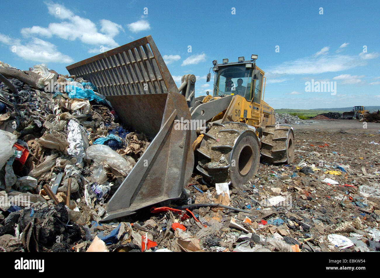 excavator on a dumping ground - Stock Image