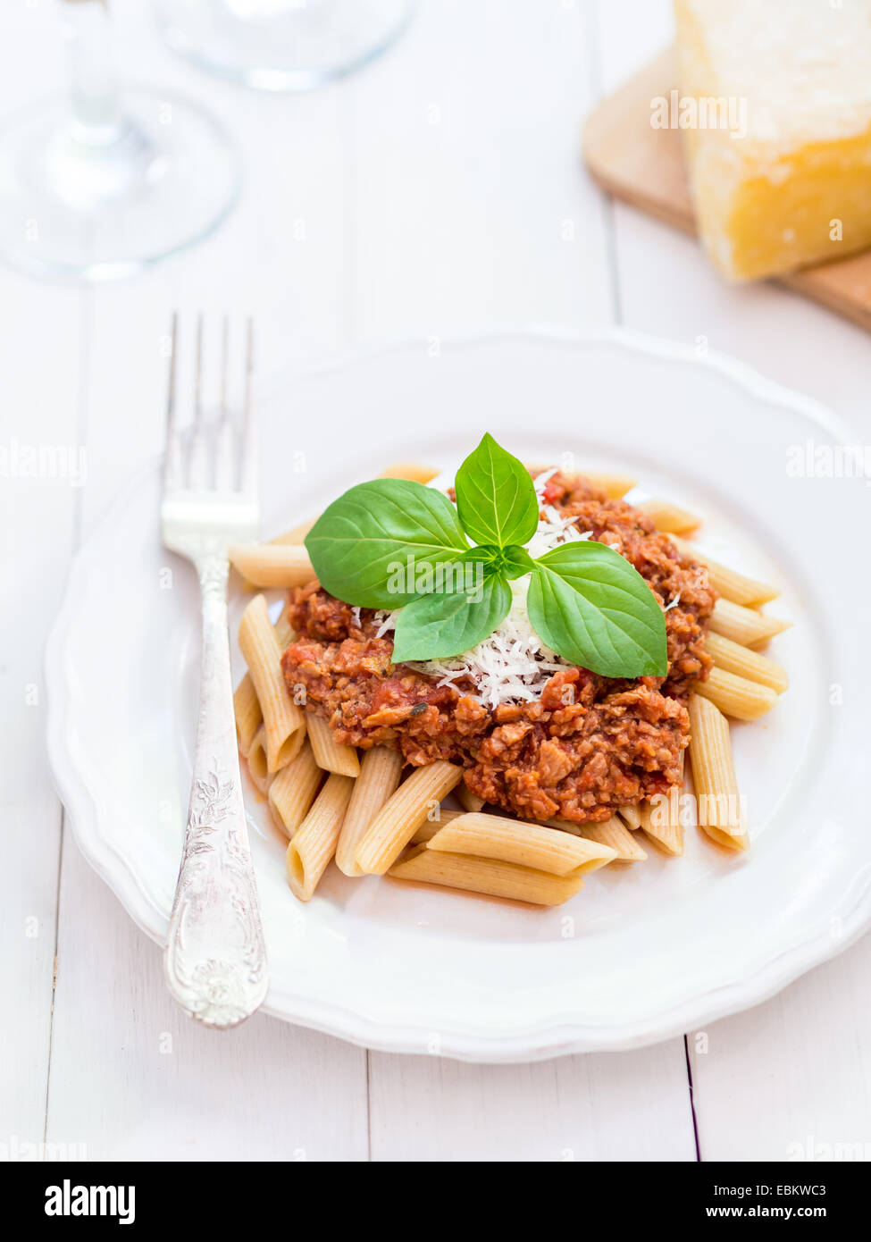 Whole grain penne pasta with vegetarian Bolognese sauce and Parmesan cheese - Stock Image
