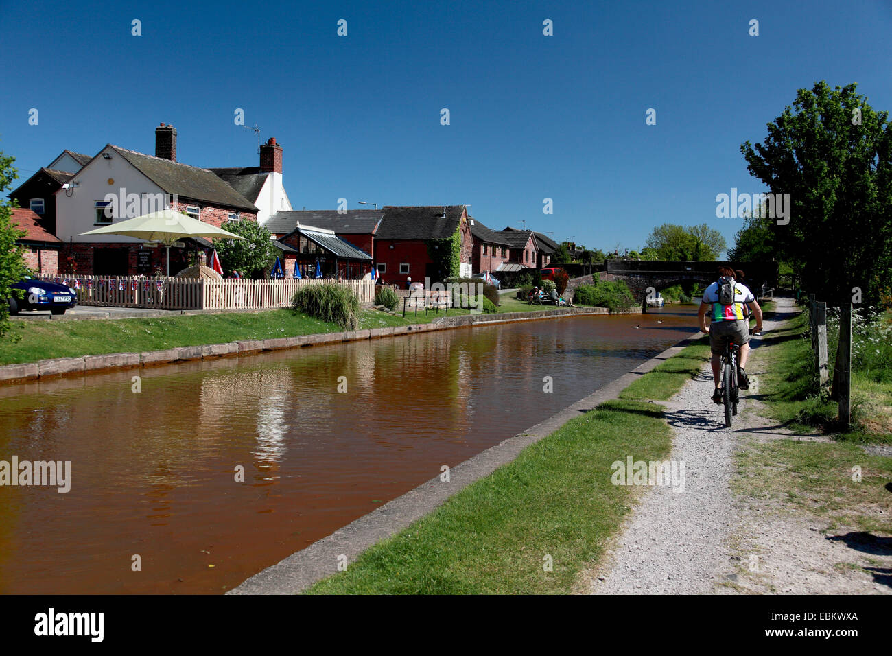 A cyclist on the towpath of the Trent and Mersey Canal at Rode Heath near Kidsgrove - Stock Image