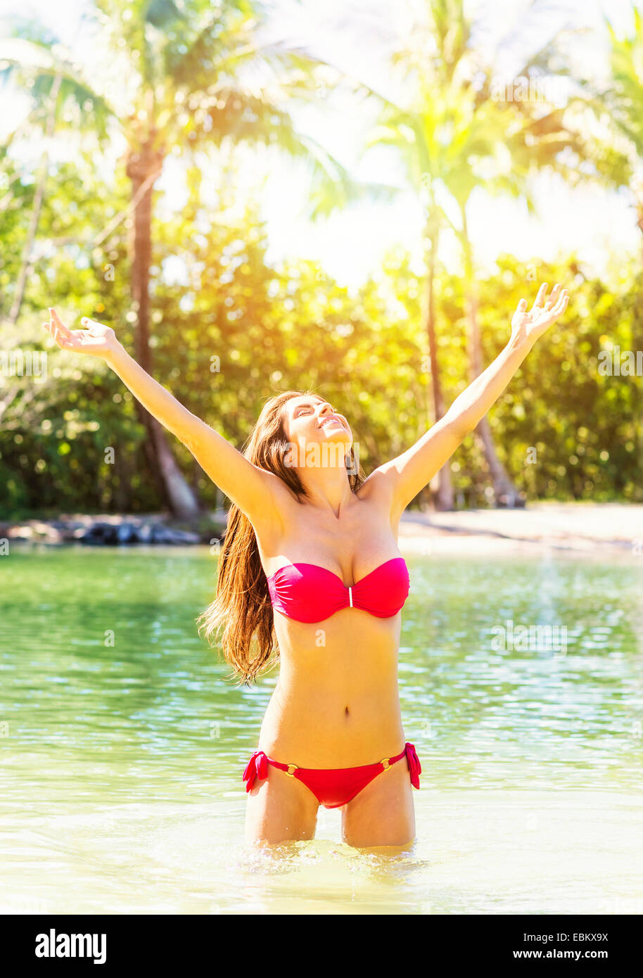 USA, Florida, Jupiter, Portrait of young woman wearing bikini standing in waters of tropical lagoon, raising arms Stock Photo