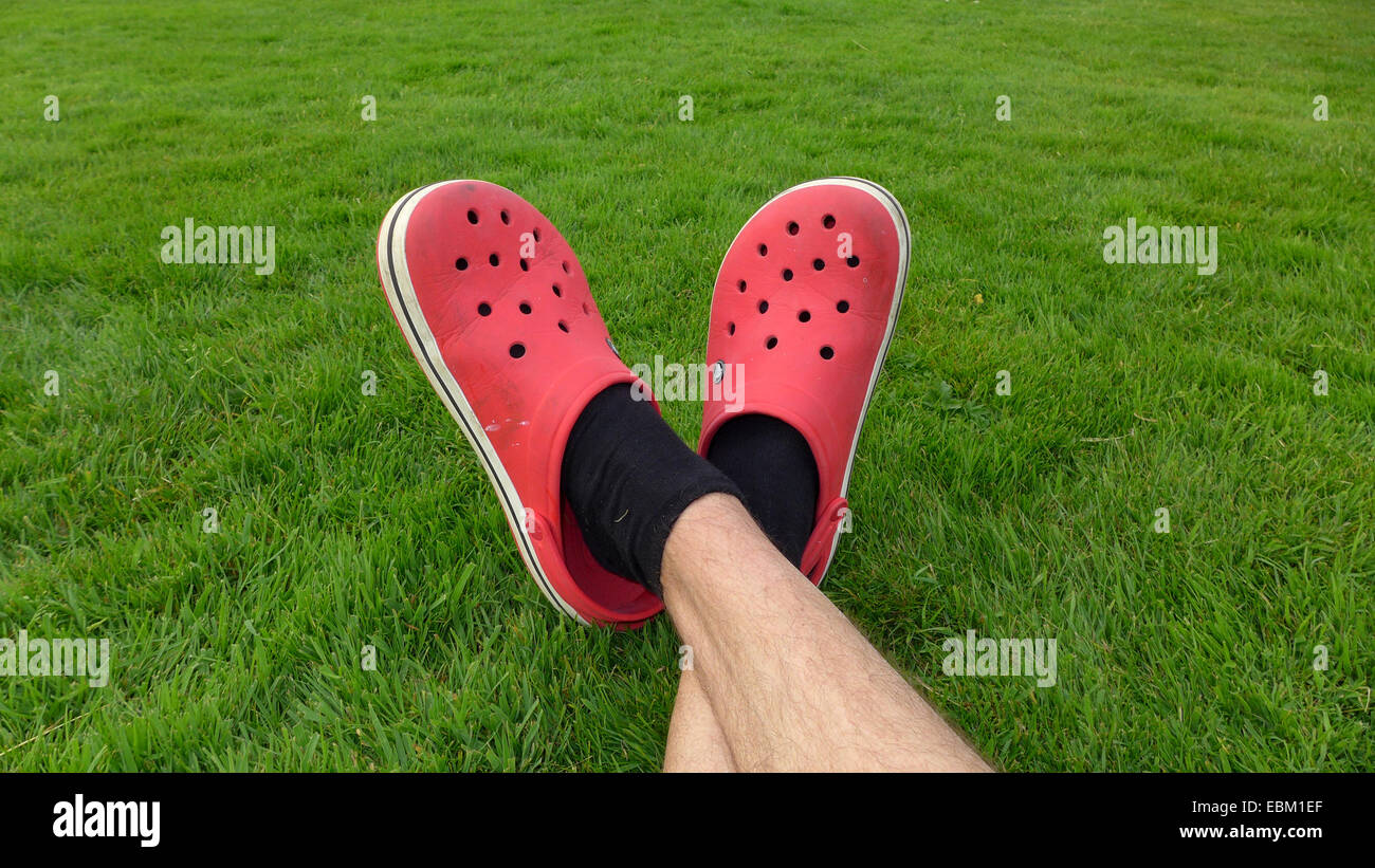 crossed legs with red rubber clogs on a green lawn - Stock Image