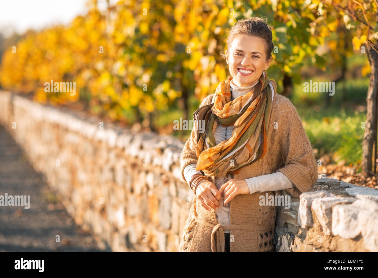 Portrait of smiling young woman in autumn park - Stock Image