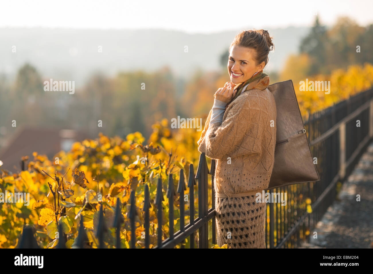 Portrait of happy young woman in autumn outdoors - Stock Image