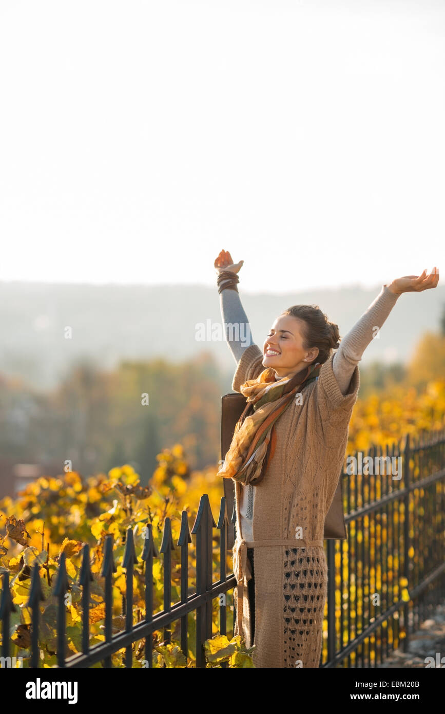 Happy young woman in autumn outdoors rejoicing - Stock Image