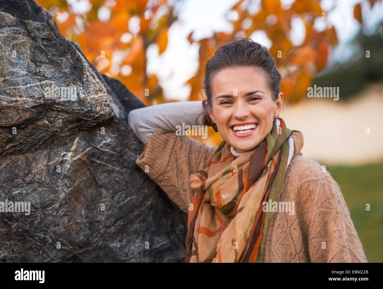 Portrait of smiling young woman in autumn outdoors in evening - Stock Image