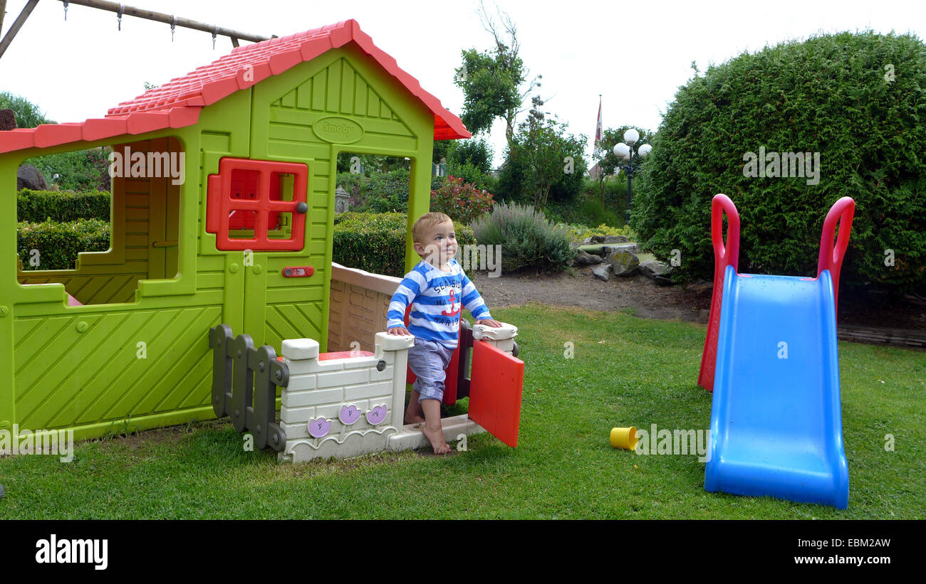 little boy playing in a garden with slide and a Wendy house Stock Photo
