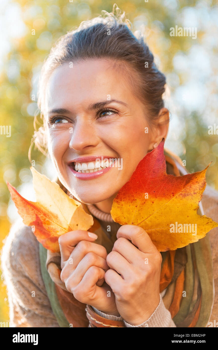 Portrait of happy young woman with autumn leafs outdoors - Stock Image