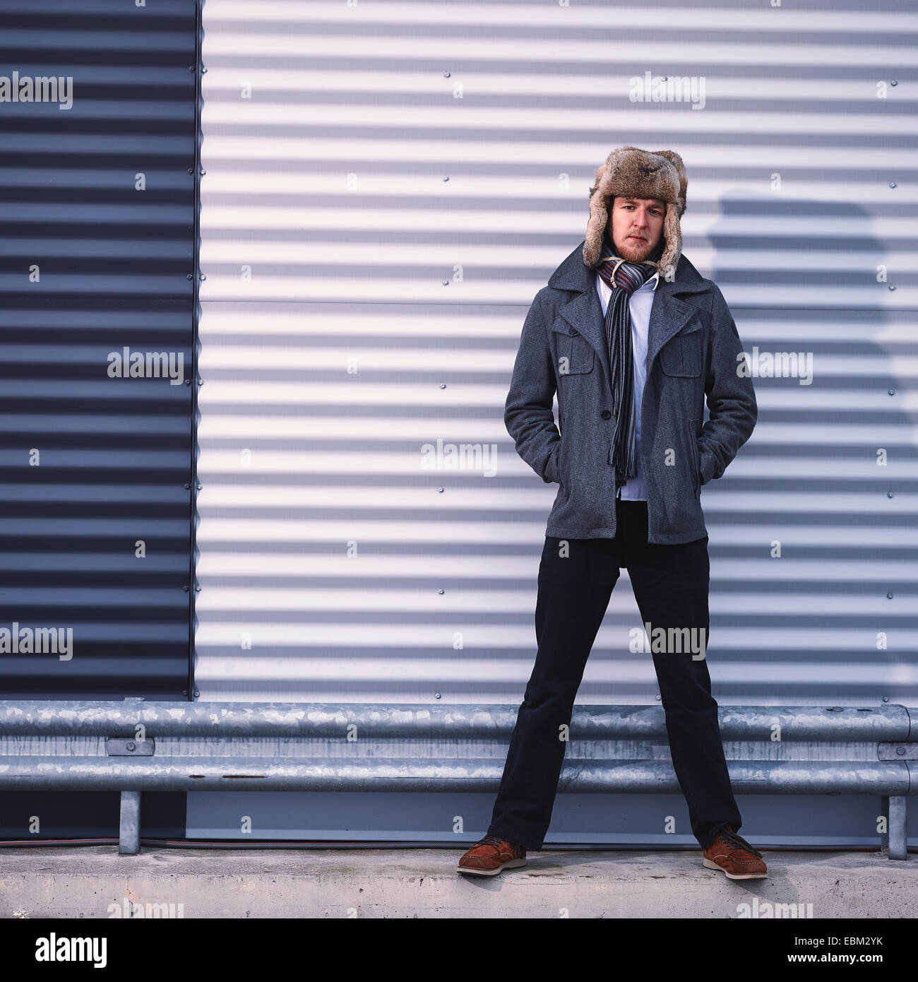 Fashionable young man wearing fur hat and warm overcoat, corrugated iron wall on background - cross processed image - Stock Image