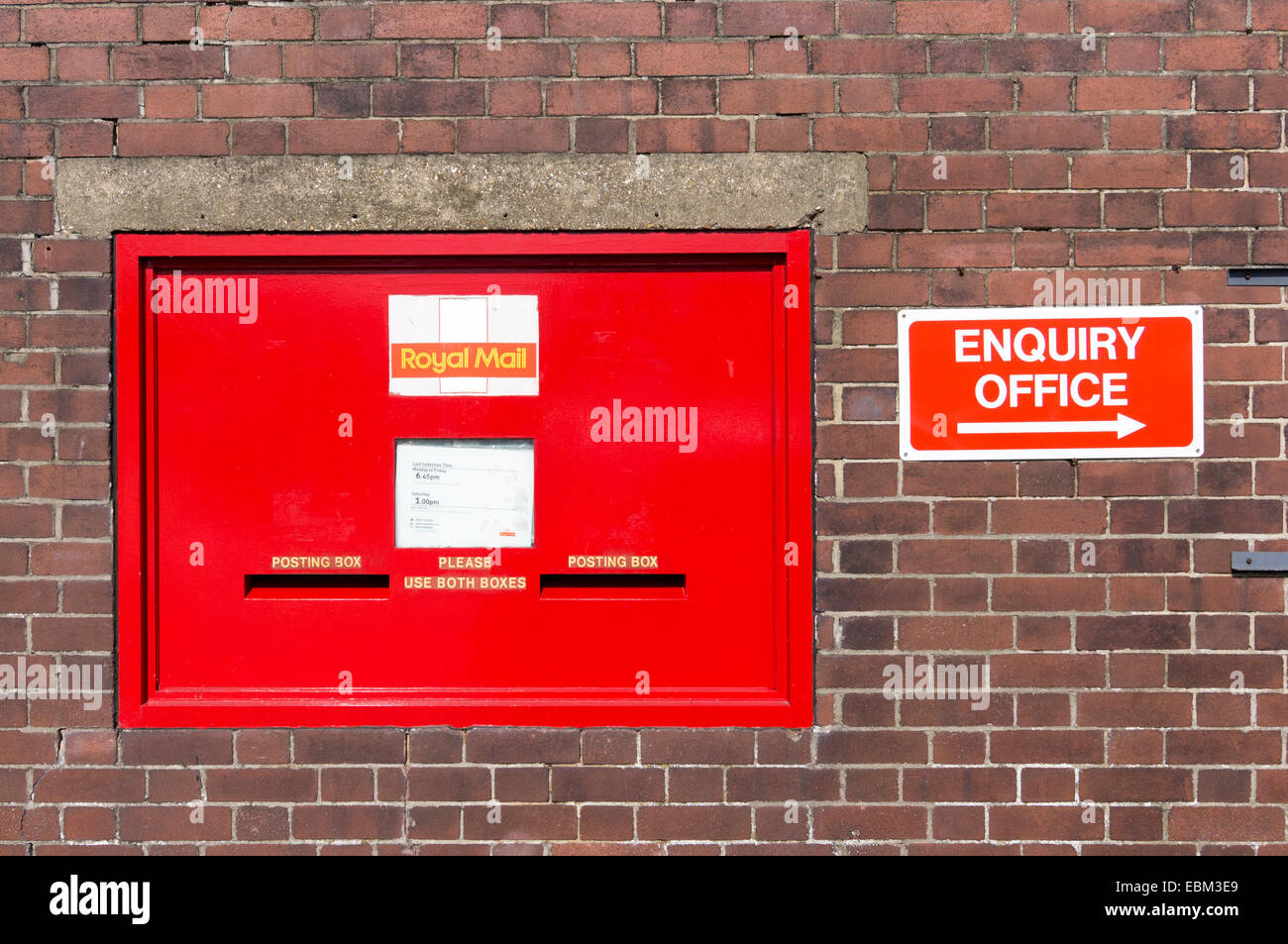 Red Royal Mail post box with enquiry office sign - Stock Image