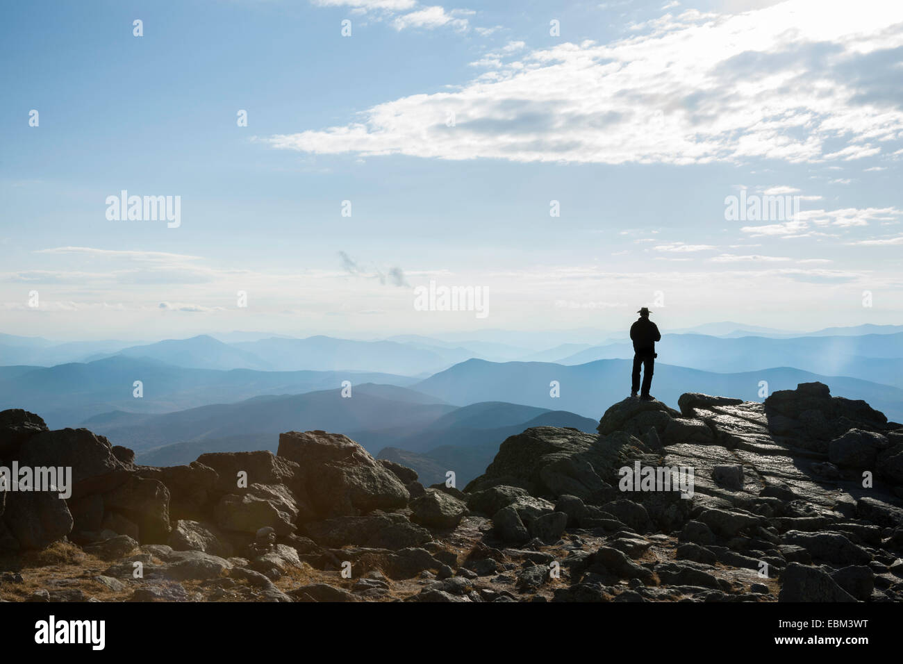 Unrecognisable silhouette of man standing on rock ledge in distance, at summit of Mount Washington, looking out - Stock Image
