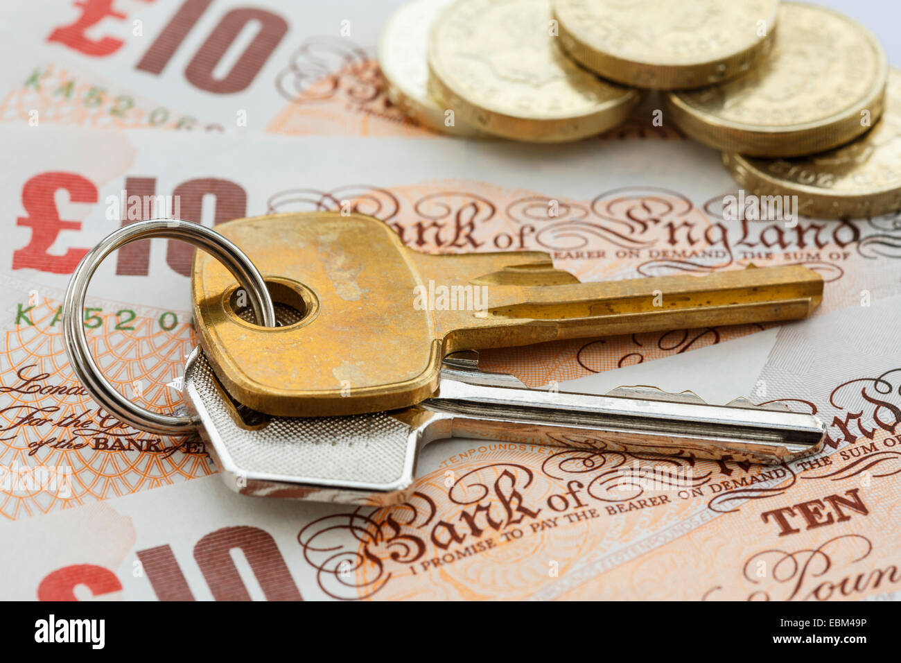 House keys on money sterling notes GBP with pound coins to illustrate UK property prices values mortgage costs concept. - Stock Image