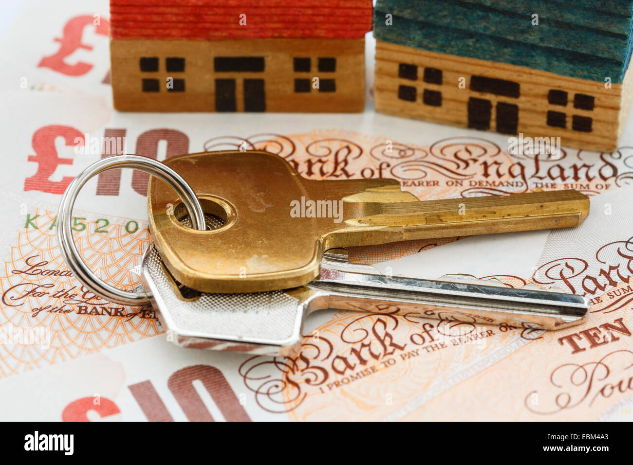 House door keys on money sterling ten pound notes GBP with two houses to illustrate property ladder and portfolio - Stock Image