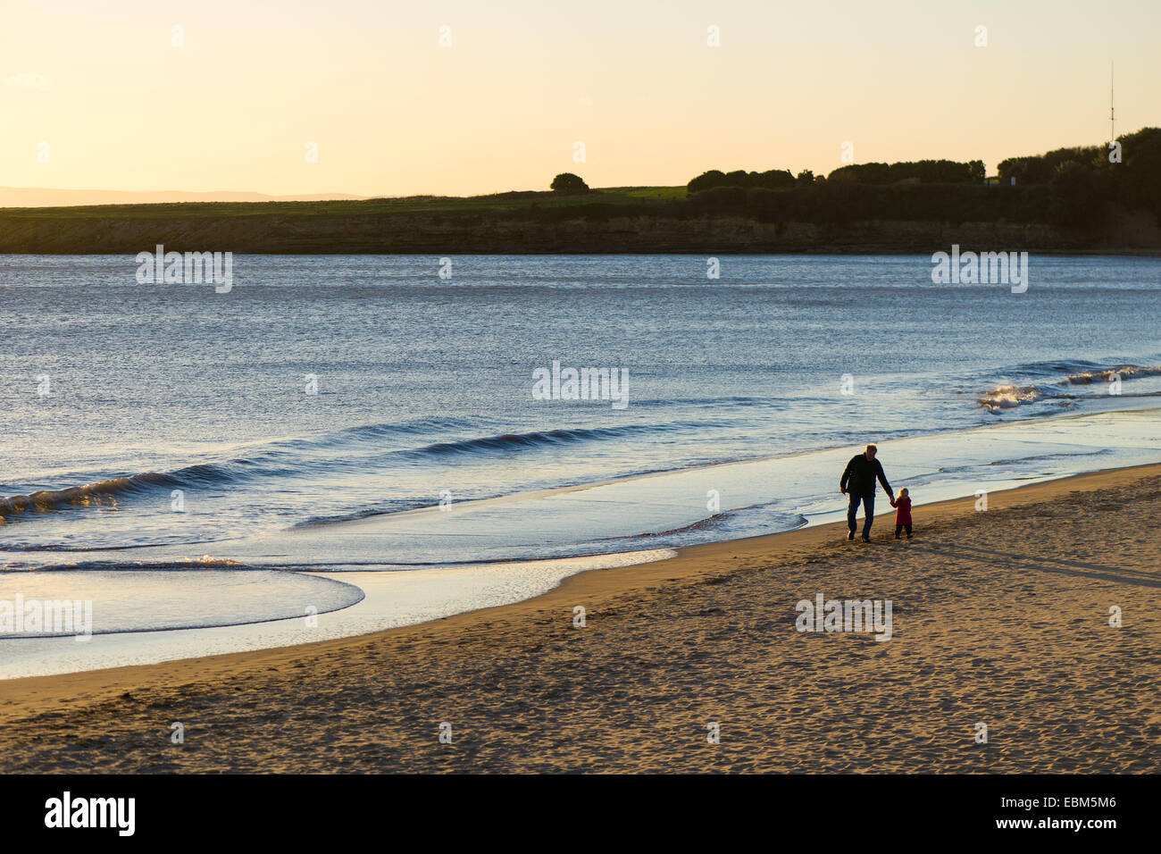 People walk along the beach in Barry Island, Wales, UK, at sunset. Stock Photo