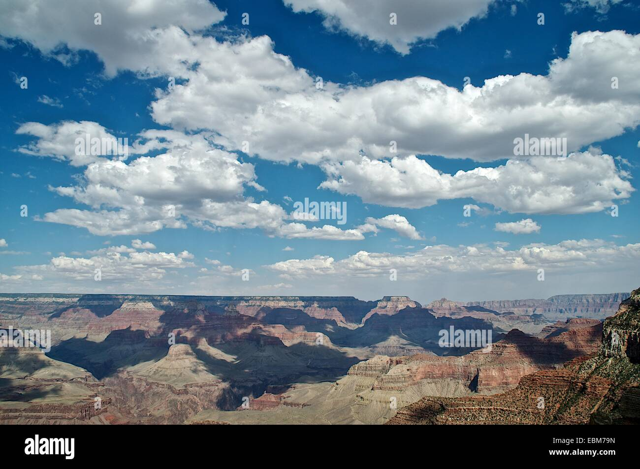 Fluffy clouds and blue sky cast shadows over the Grand Canyon, USA - Stock Image