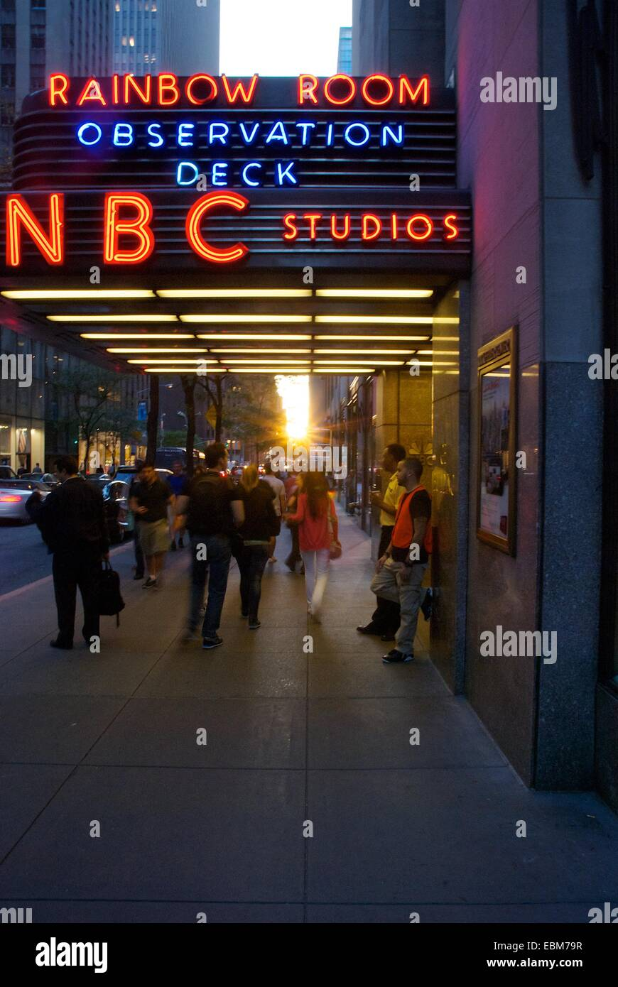 The sun setting outside NBC studios in New York City as people move outside - Stock Image
