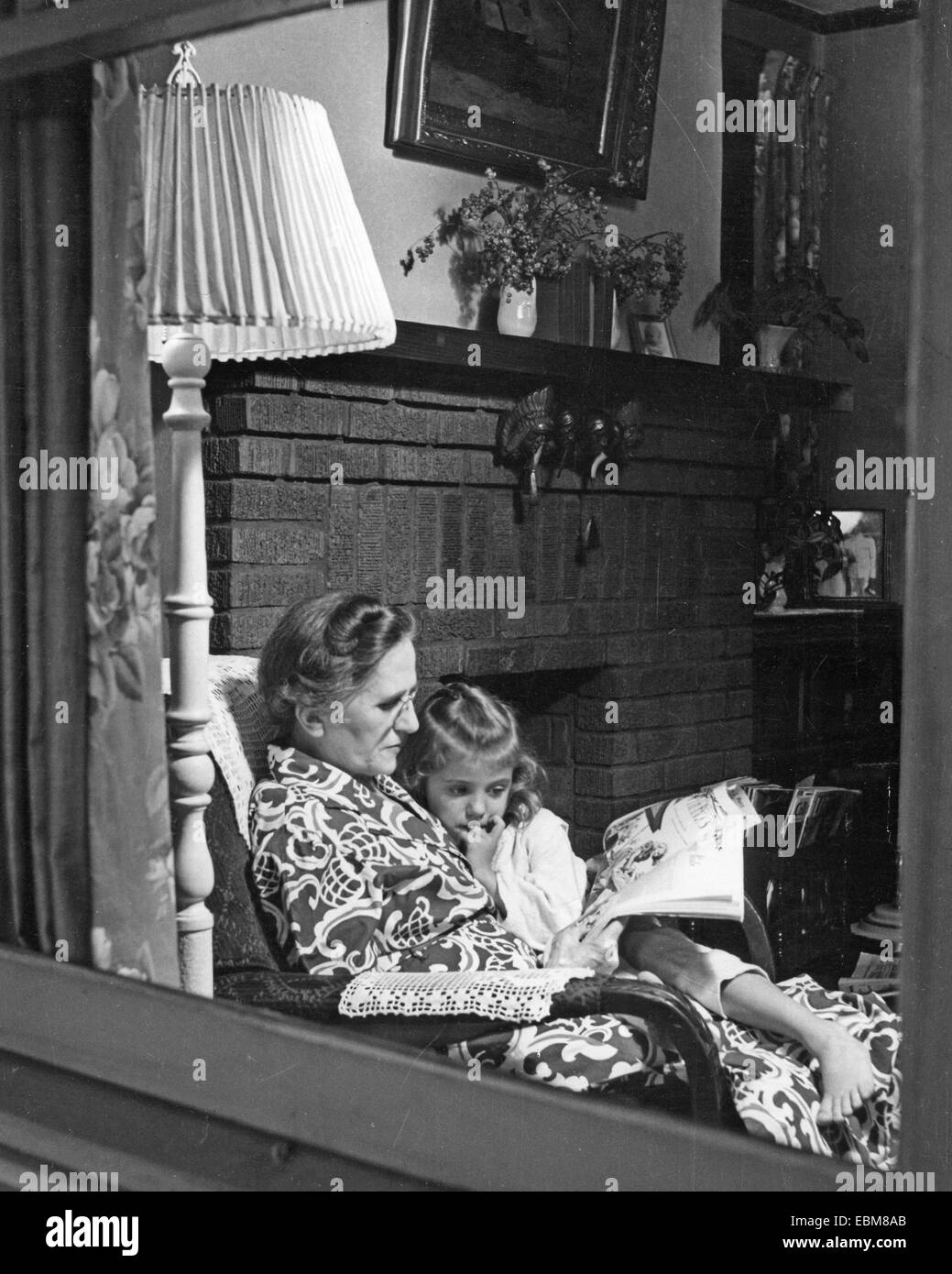 AMERICAN FAMILY GROUP - Grandmother reads a story about 1945 - Stock Image