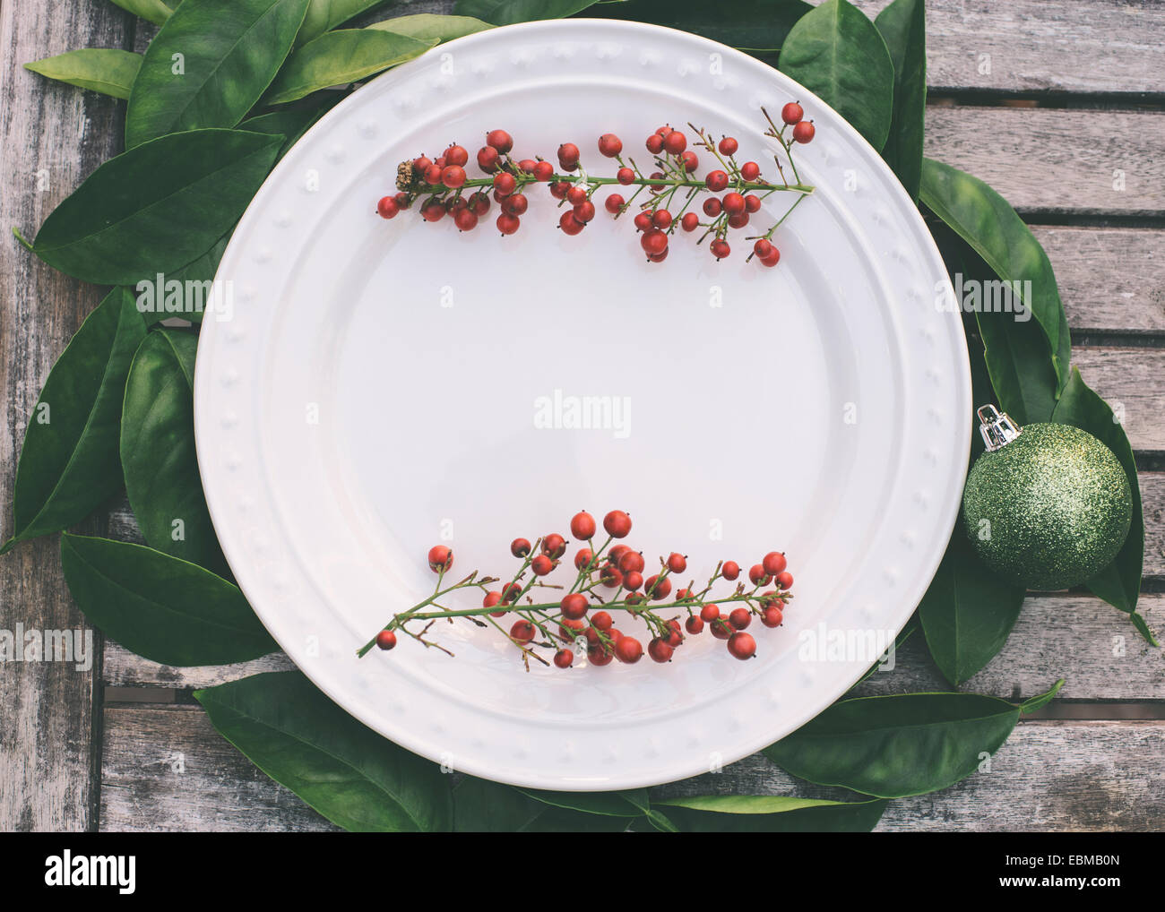 Rustic Christmas table setting with red berries bordering a white ...