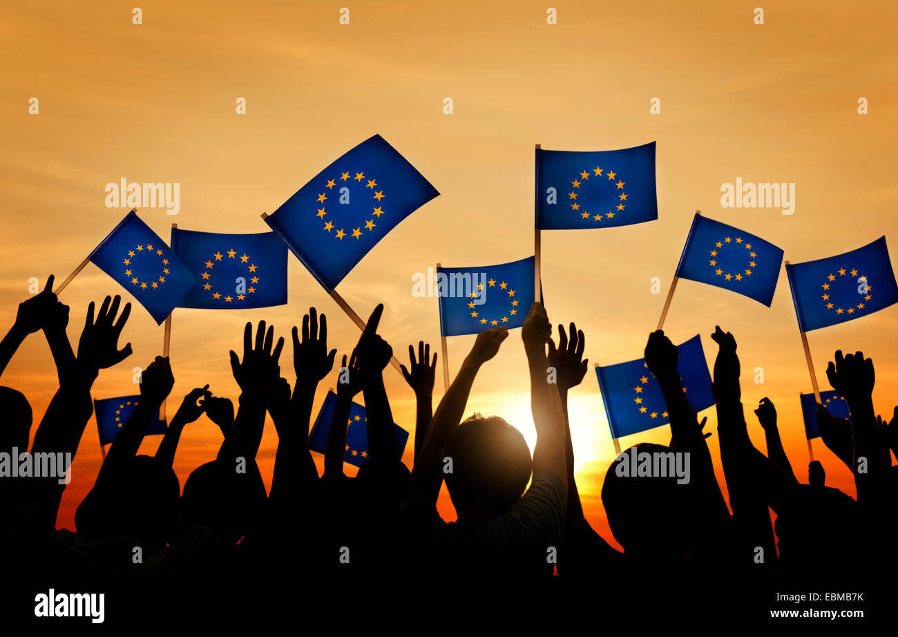 Group of People Waving European Union Flags in Back Lit - Stock Image