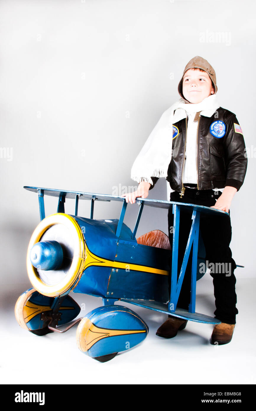 Retro child pilot with antique pedal plane - Stock Image