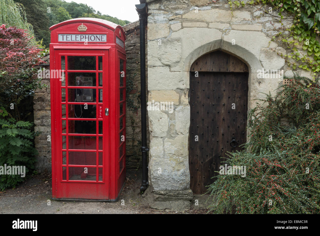 Red telephone box next to an old studded wooden door in a cotswold stone building, Castle Combe, Wiltshire, England - Stock Image
