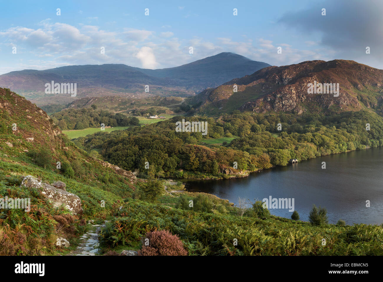 The early morning sun lights up the hills and mountains surrounding Llyn Dinas, Snowdonia, North Wales Stock Photo