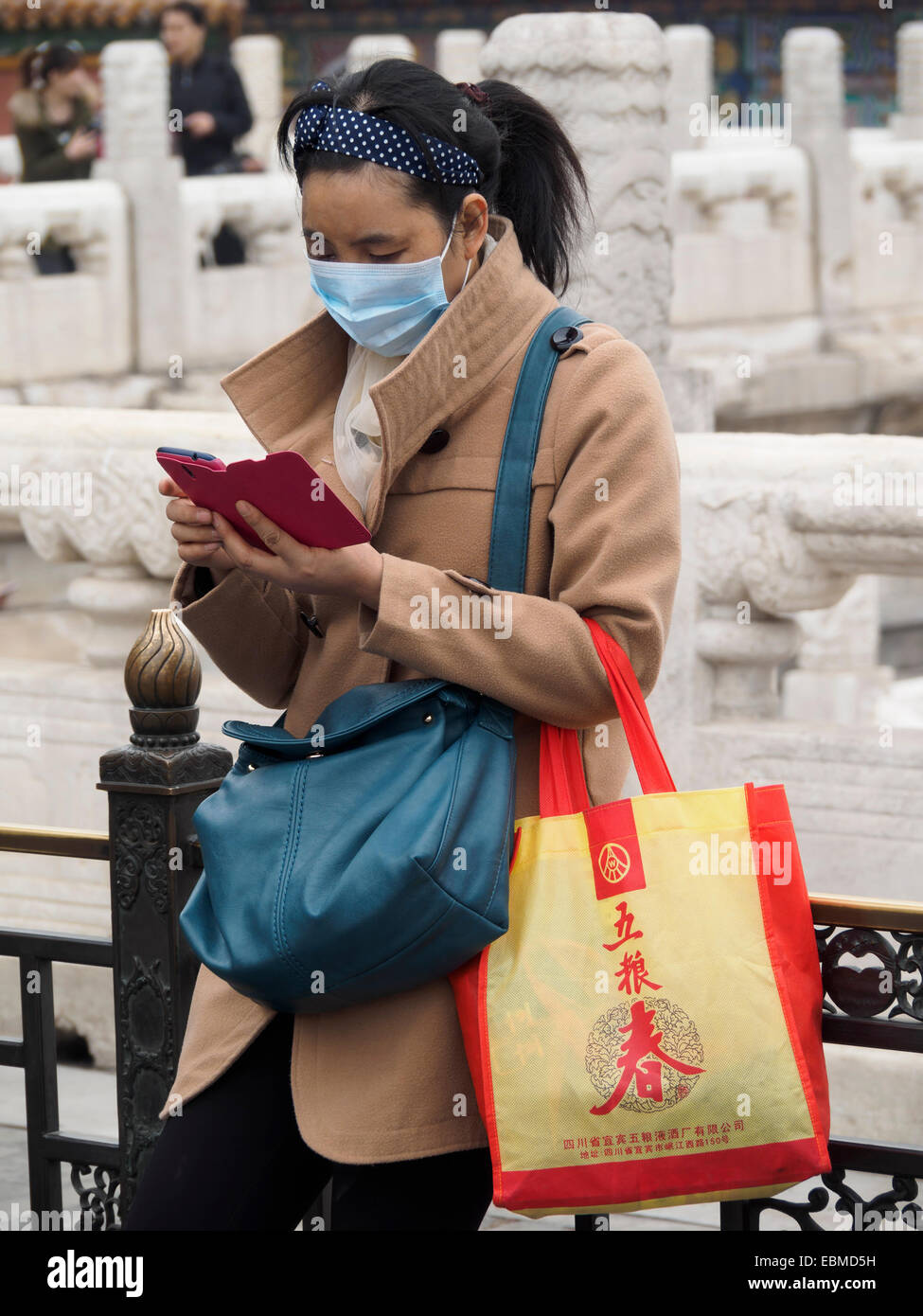 Chinese woman using smartphone while wearing a pollution mask because of heavy smog - Stock Image
