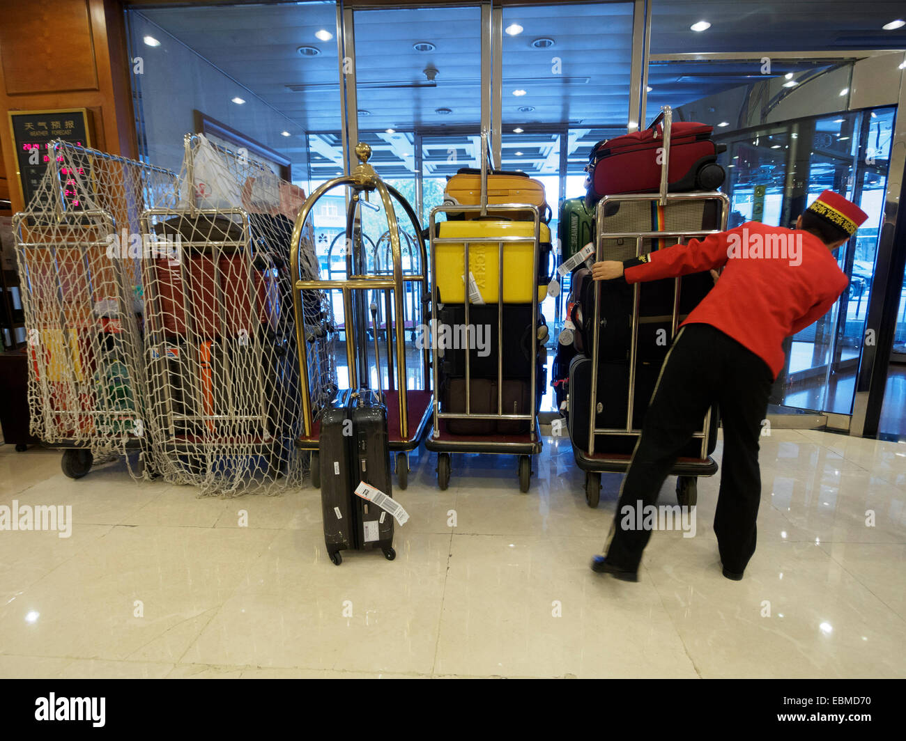 Bellboy in uniform pushing luggage in an Hotel - Stock Image