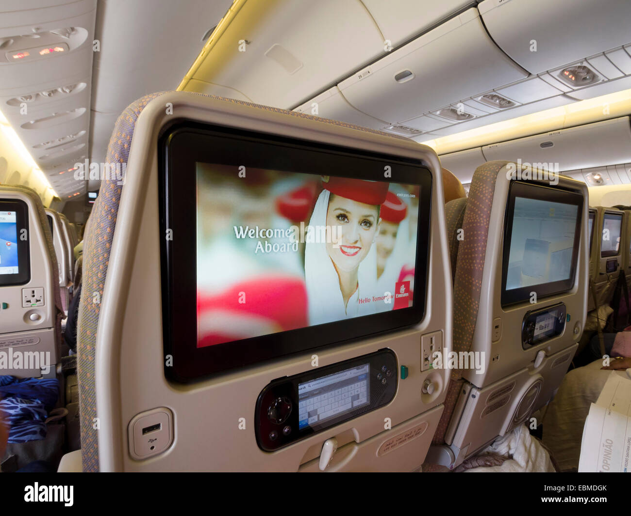 Entertainment system screens inside the cabin of a Emirates Boeing 777 airplane - Stock Image