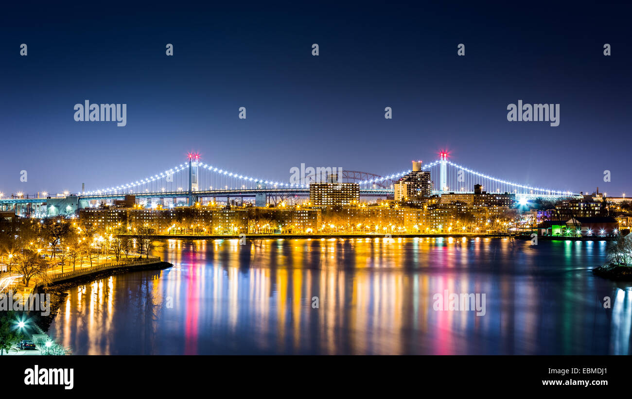 Queens cityscape by night framed by the illuminated RFK bridge (aka Triboro bridge) as viewed from Roosevelt island - Stock Image