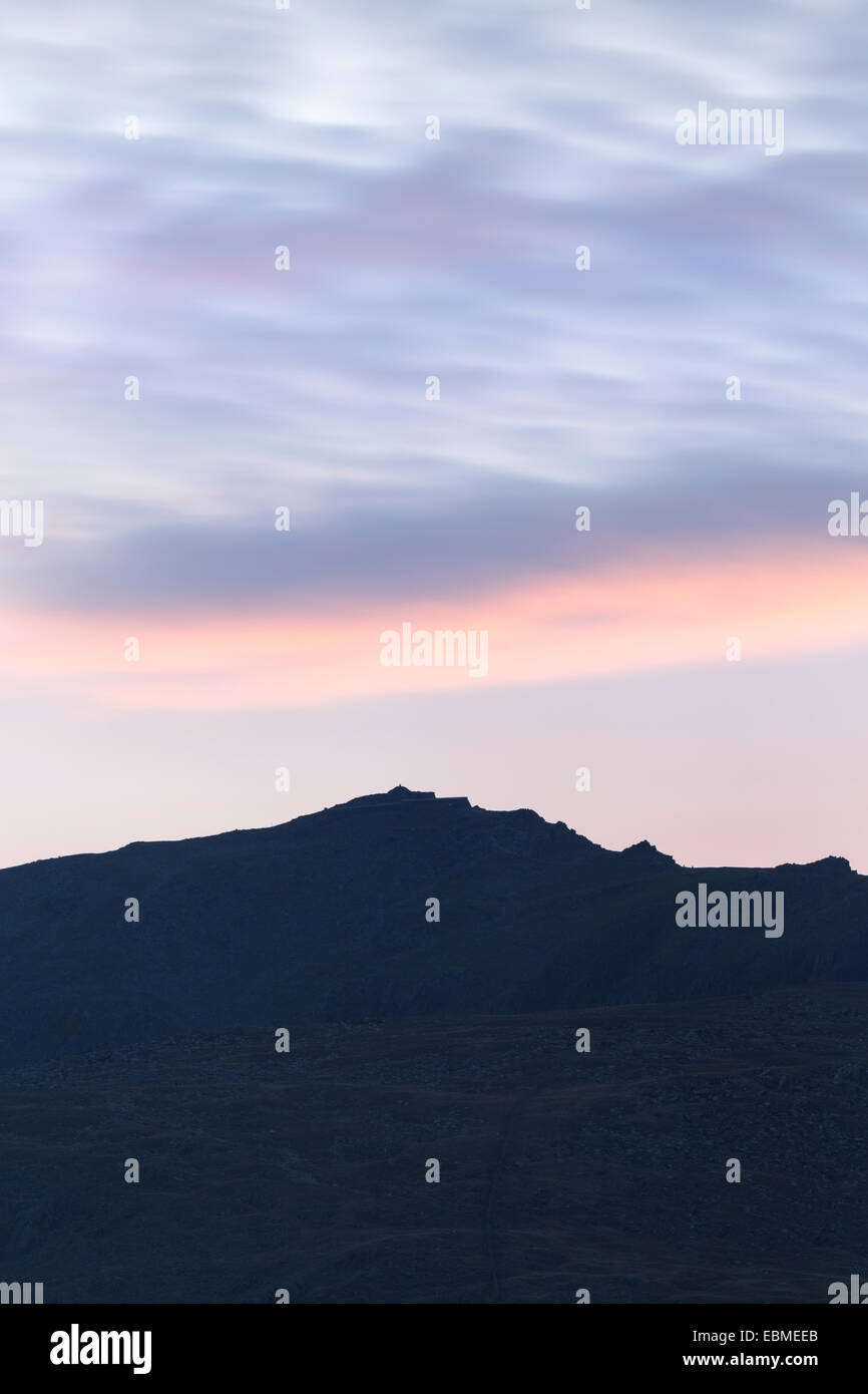 The early morning sun lights up the clouds above Mount Snowdon, Snowdonia, North Wales. Stock Photo
