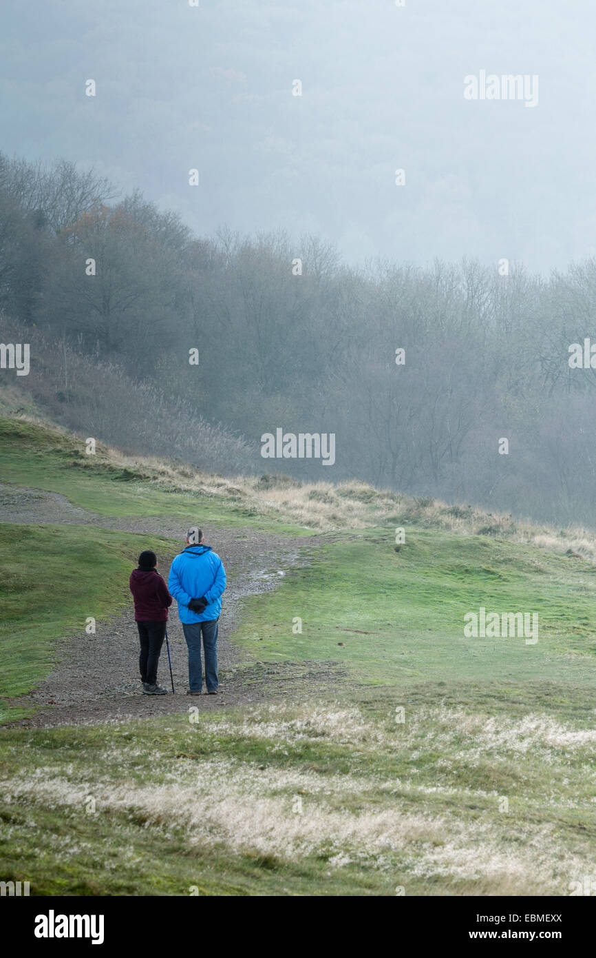 Two walkers on a path on the Malvern Hills looking out over Herefordshire. Stock Photo