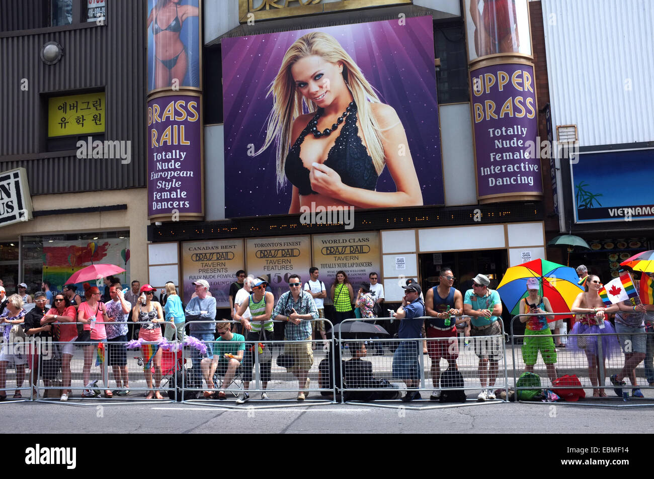 A crowd of spectators standing in front of a strip club, line the 2014  World Pride route in Toronto.