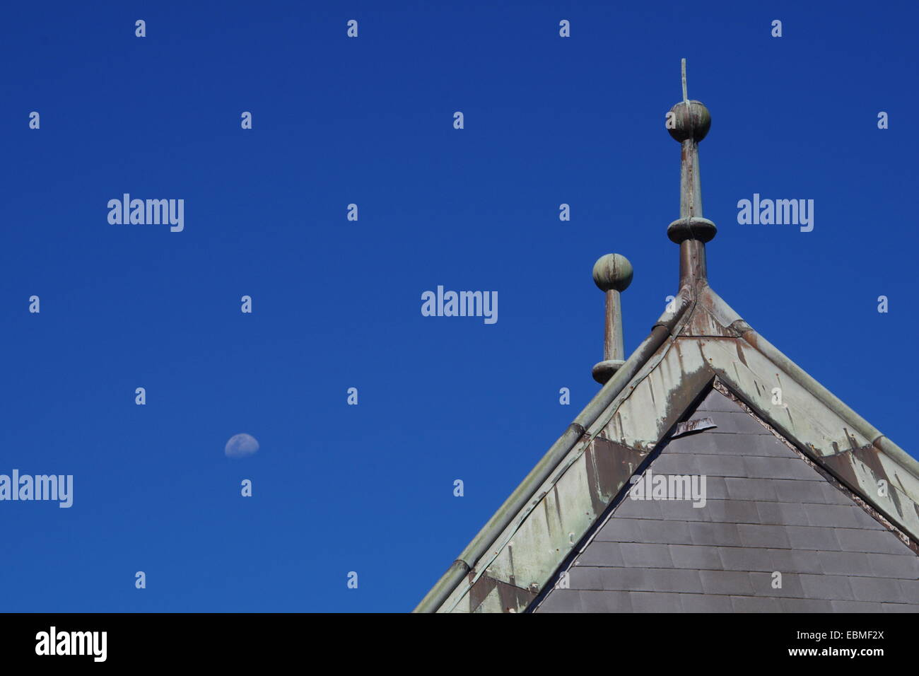 Valve house roof and the moon on a bright sunny day. - Stock Image