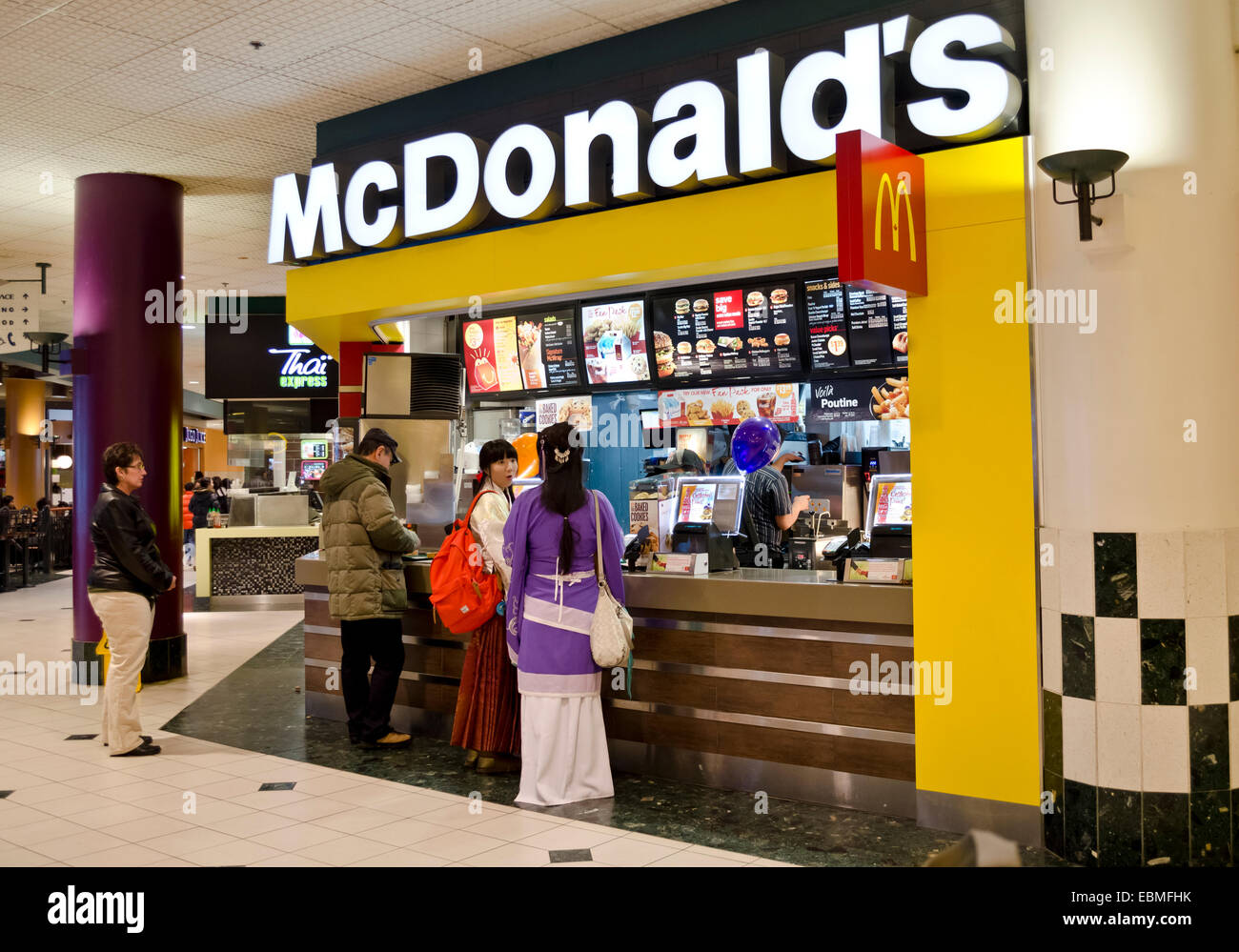 Customers at McDonald's restaurant in a food court at Waterfront Centre in downtown Vancouver. Asian women in - Stock Image