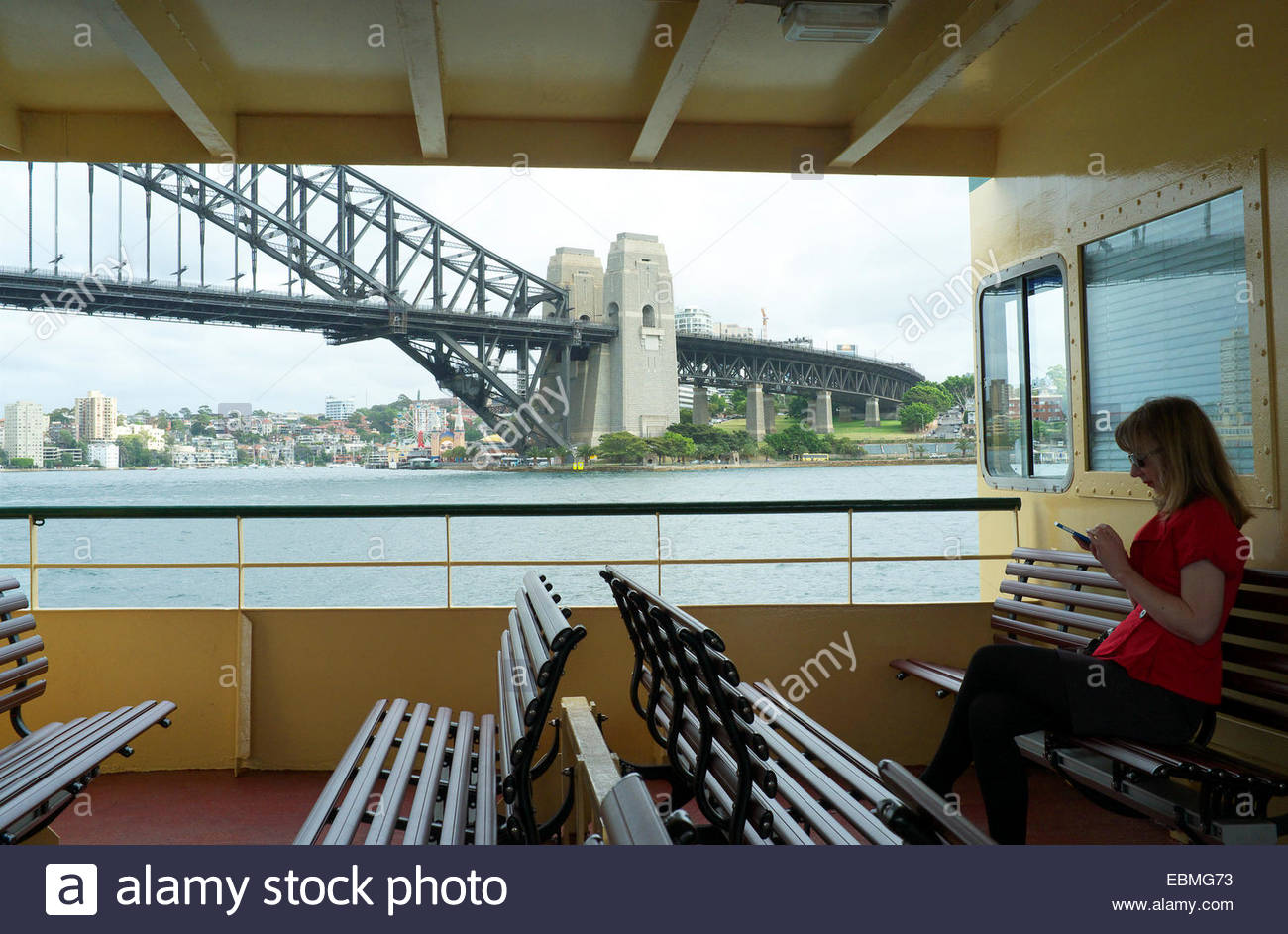 Woman passes the Sydney Harbour Bridge whilst tapping her mobile phone on her commute to Sydney, NSW, Australia. - Stock Image