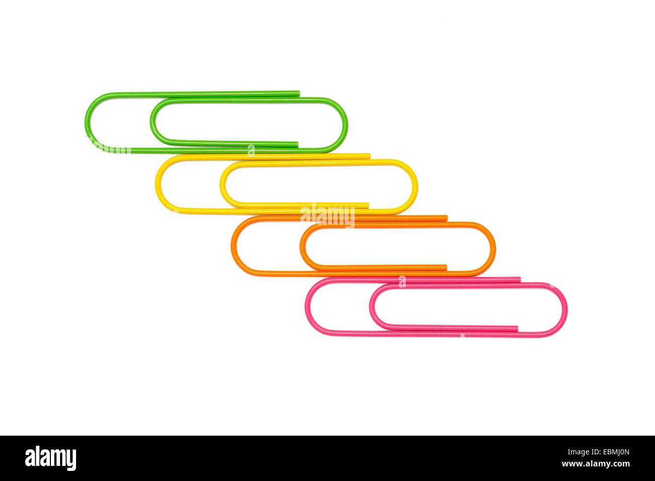 Giant paper clips arranged on a white paper background - Stock Image