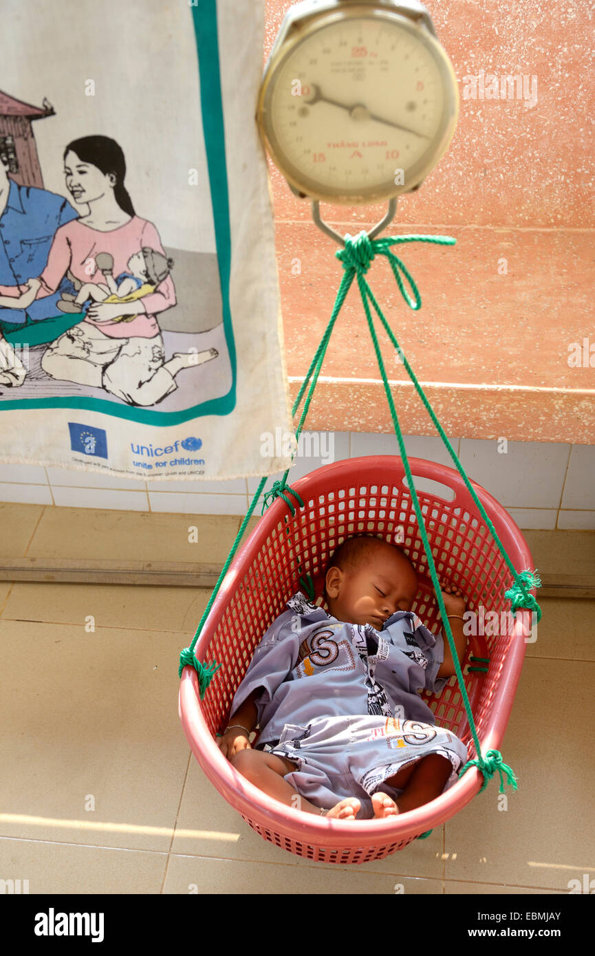 Child being weighed in a basket hanging on a scale, Sophi, Banteay Meanchey province, Cambodia - Stock Image