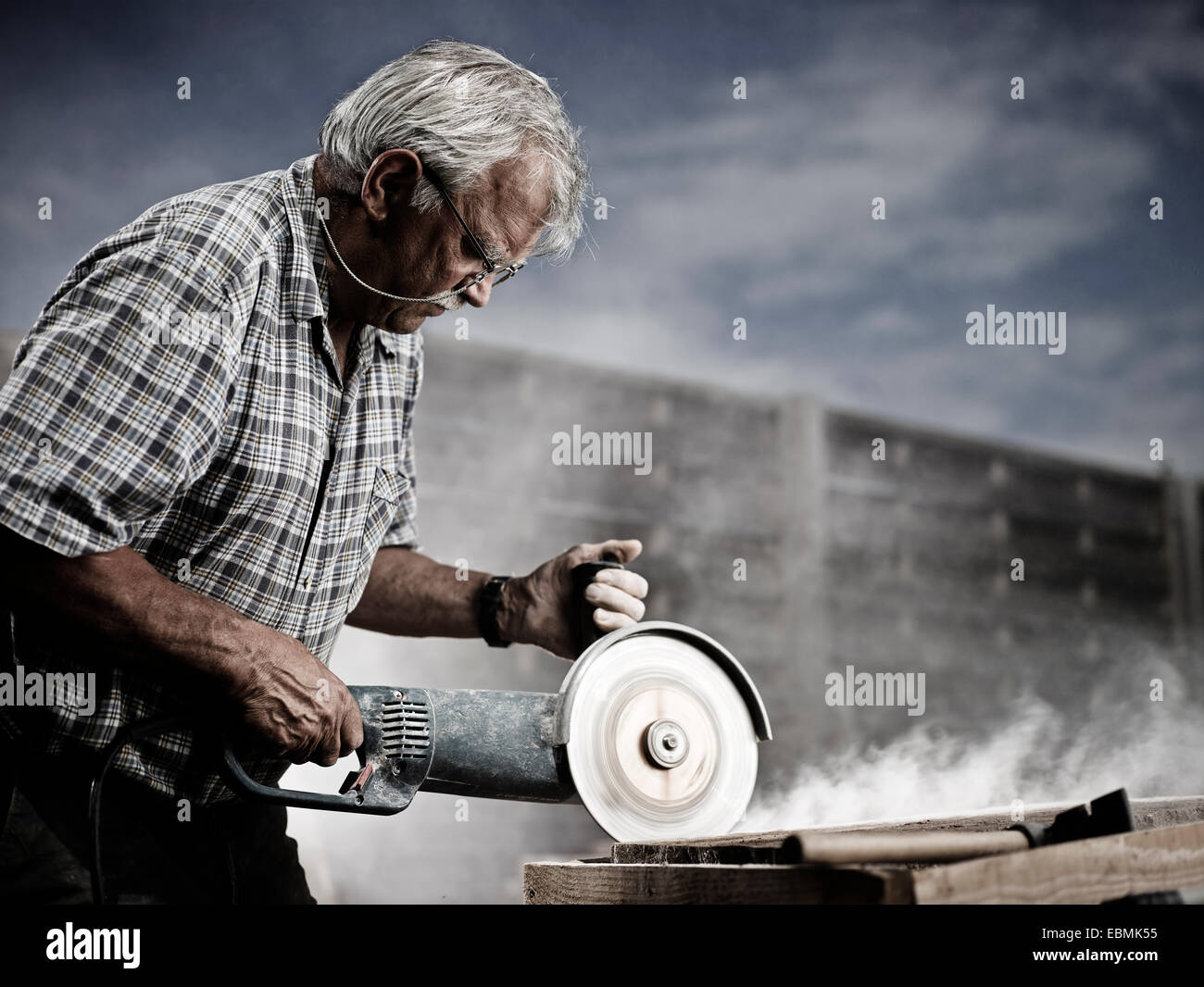 Stonemason cutting a stone slab with an angle grinder with a cutting disc, Reith im Alpbachtal, Kufstein District, - Stock Image