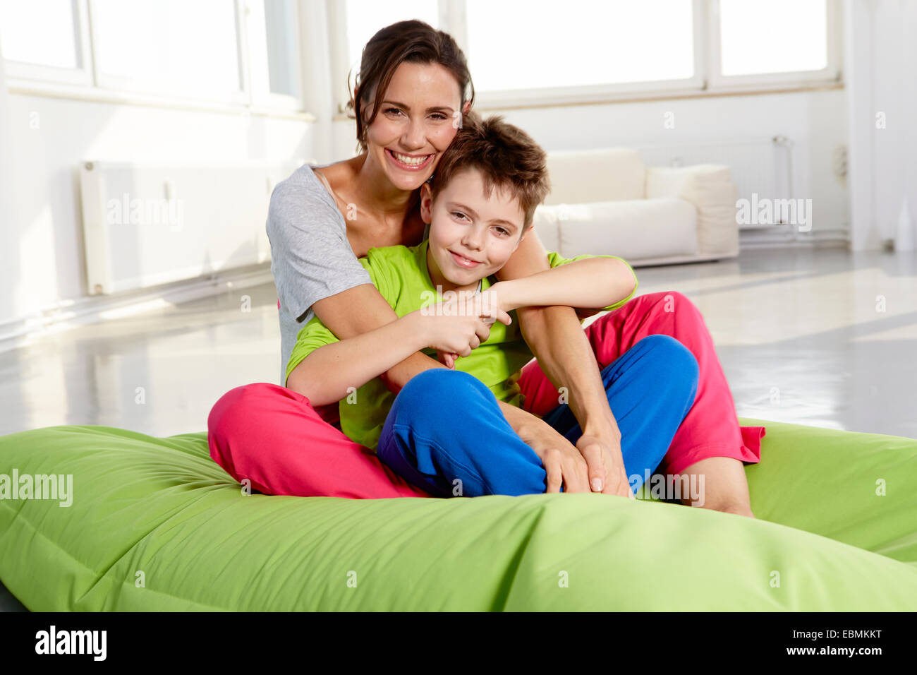 Mother and son in casual clothes sitting on a beanbag in a loft, Germany - Stock Image