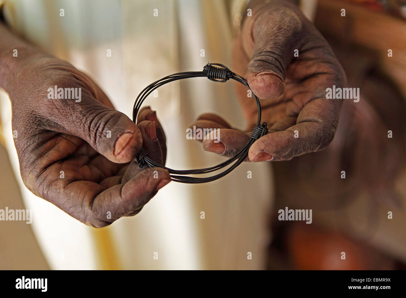 Hands holding a bangle made from elephant tail bristles, Garoua, North Region, Cameroon - Stock Image