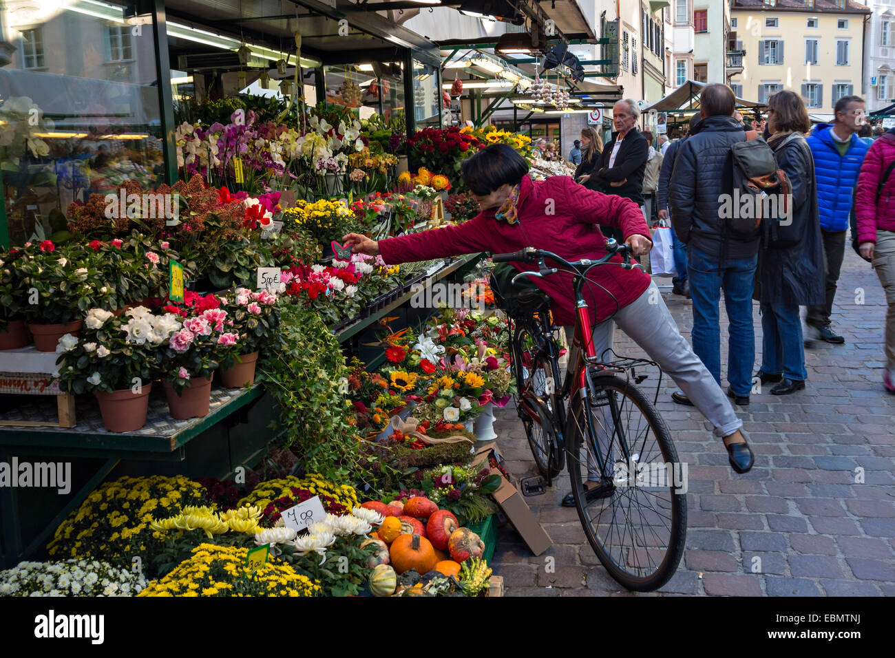 Woman with bicycle at street market flower stand (shop), Bozen,  Bolzano, South Tyrol, Italy, Europe - Stock Image